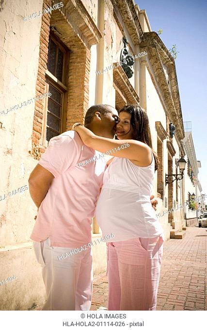 Pregnant young woman embracing a mid adult man