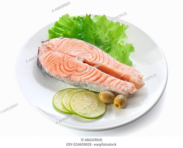 Steamed salmon with fresh green lettuce, pieces of lime and green olives on the white plate