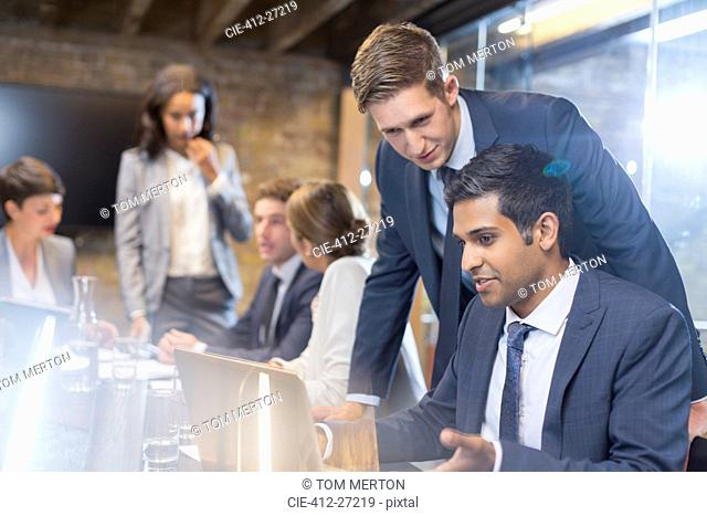 Businessmen working at laptop in conference room meeting