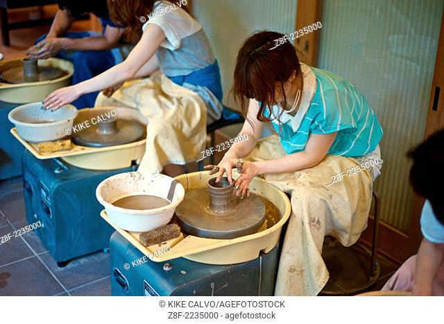 Tourists learn the arts of pottery on a studio on Sannen-zaka Street, which leads up to Kyoto's famous Kiyomizudera Temple