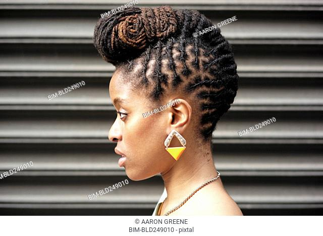 Profile of African American woman with braids near metal wall
