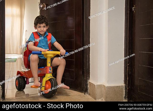 17 June 2020, Egypt, Cairo: Malek Mohamed, 5 years old, poses for a picture while wearing his school uniform and playing with his bicycle