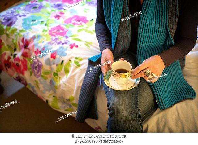 Midle Age Lady, relaxed and calm, seating on the bed side with a cup of coffee in hand