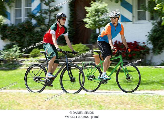 Man and teenage boy on a bicycle tour with trekking bikes