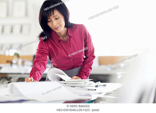 middle aged business woman reviewing book