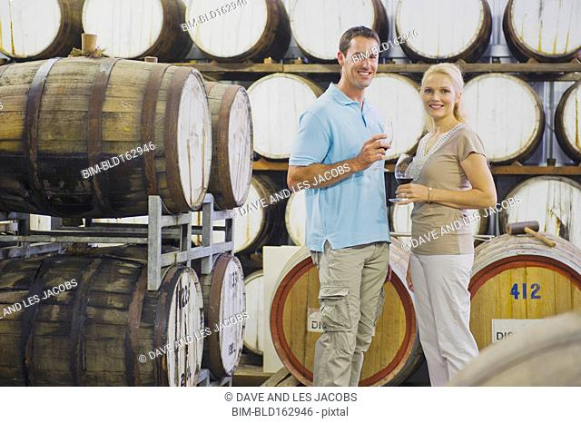 Caucasian couple tasting wine in winery