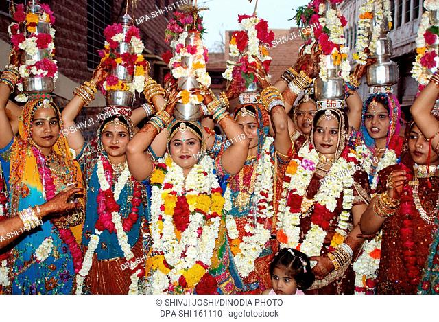 Rajasthani Marwari women with silver Lotiyan on head on occasion of Gangaur ; Jodhpur ; Rajasthan ; India NO MR