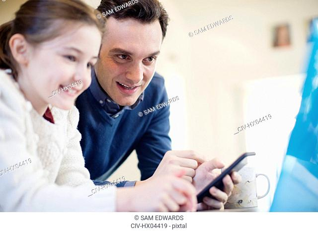 Father with smart phone using laptop with daughter