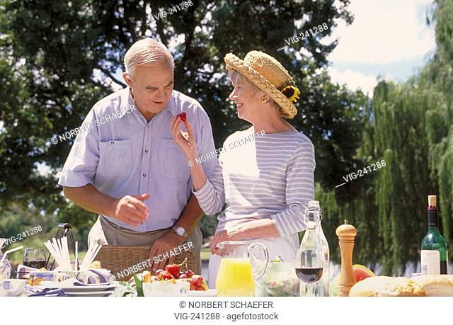 park-scene, portrait, senior-couple enjoys a summer day in the garden at a picknick with strawberries and a glass of red wine  - GERMANY, 05/04/2004