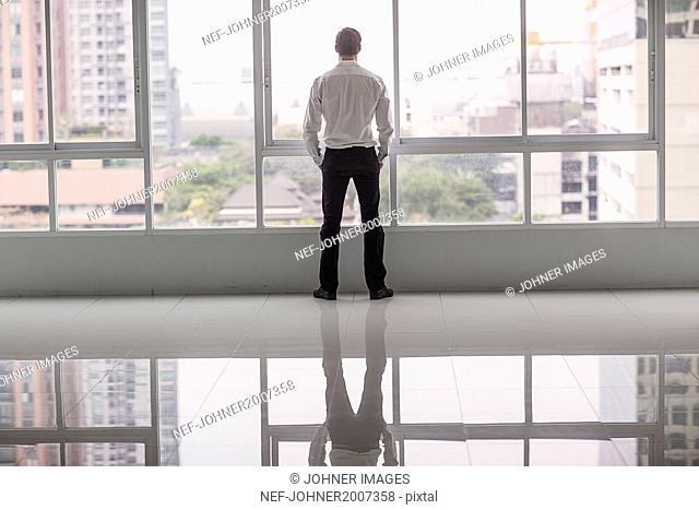 Businessman looking through window in office building