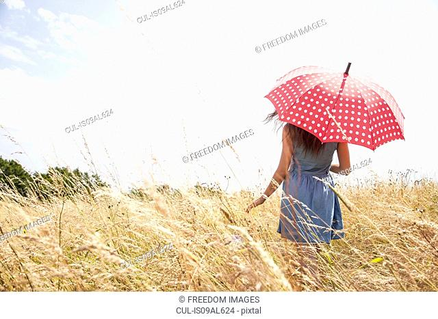 Young woman in field with umbrella