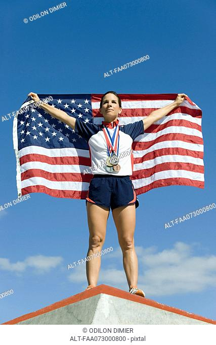 Female athlete being honored on podium, holding up American flag