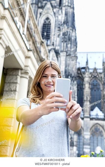 Germany, Cologne, portrait of young woman taking a selfie with smartphone