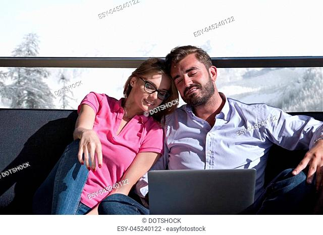 Young couple relaxing at home using laptop computers reading in the living room near the window on the sofa couch