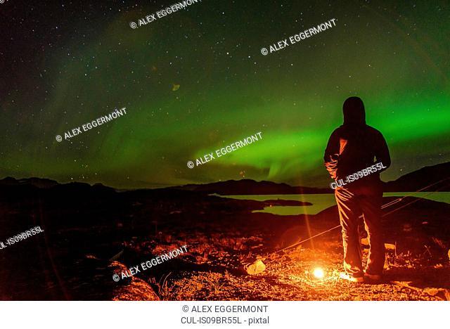 Man watching aurora borealis, Narsaq, Vestgronland, Greenland