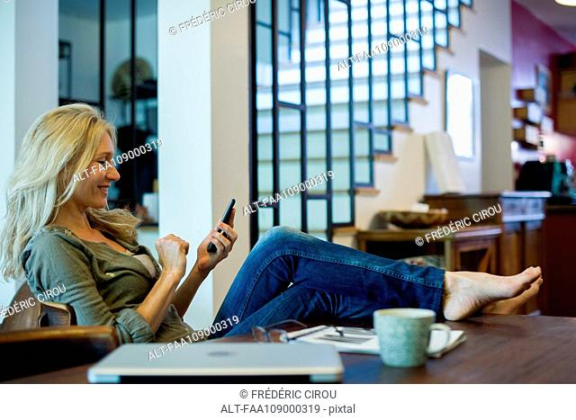 Woman relaxing at home with smartphone