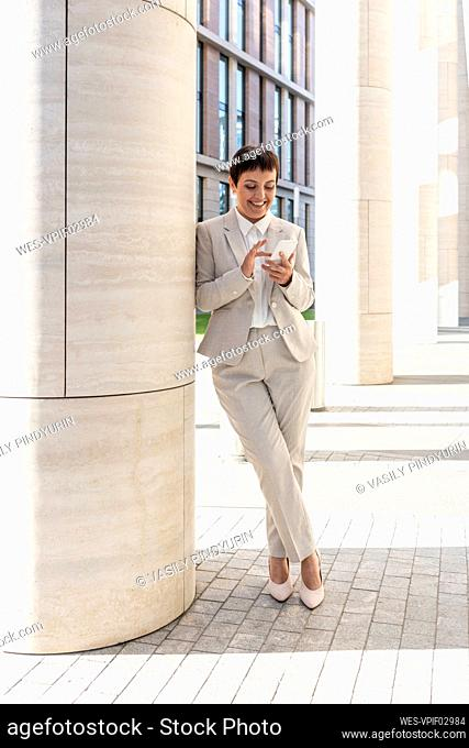Businesswoman using phone while leaning on pillar in city