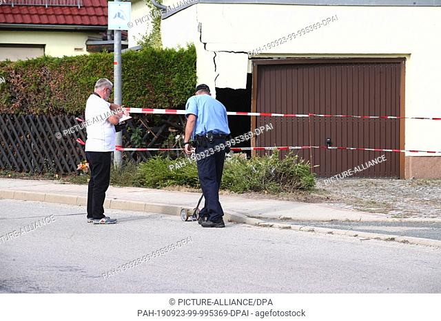 23 September 2019, Thuringia, Bad Sulza: A police officer and an expert measure an accident site in Reisdorf near Bad Sulza. Here on Sunday (22.09