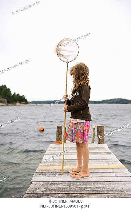 Girl holding fishing net on jetty