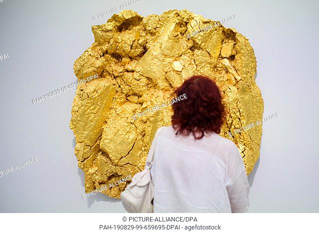 """29 August 2019, Berlin: A visitor looks at the golden plaster cast """"""""Acker"""""""" by the artist Asta Gröting in the exhibition """"""""Nah am Leben"""