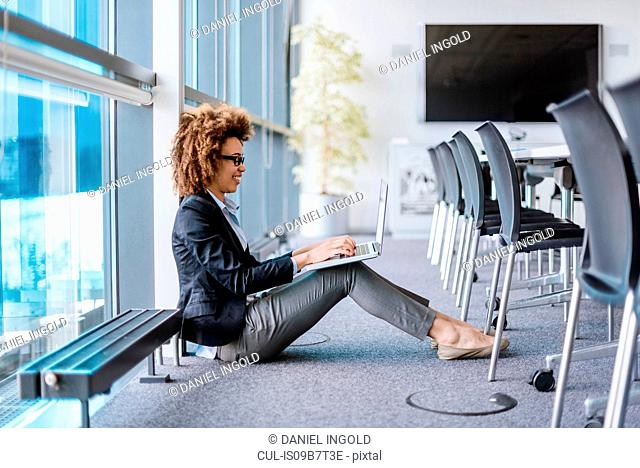 Young businesswoman sitting on floor using digital tablet in boardroom