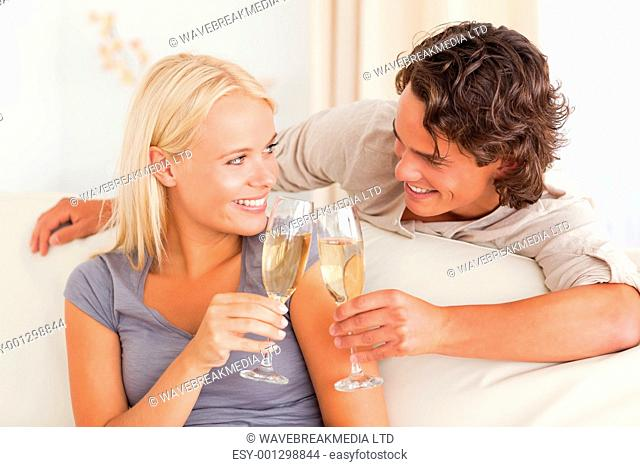 Young couple making a toast in their living room