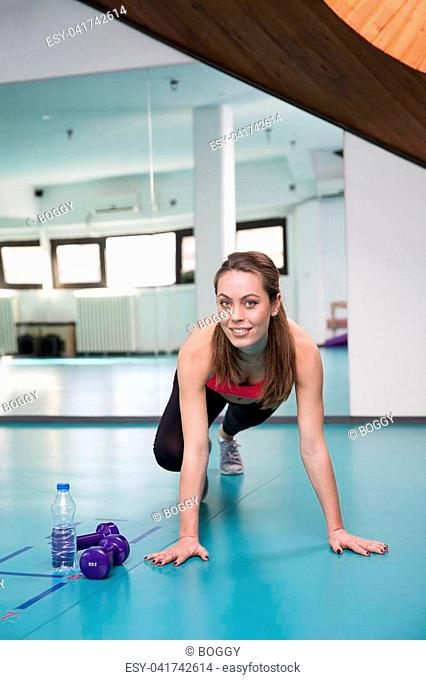 Young woman exercise in fitness studio on the floor