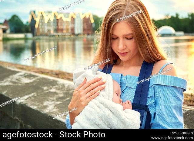 young happy mom with her sleeping baby on hands smiling, closeup portrait