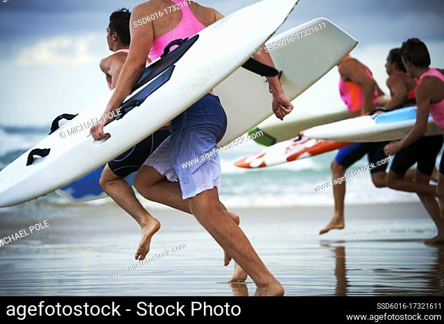 Close up of team of male surf lifeguards training and running into sea holding ocean surf skis