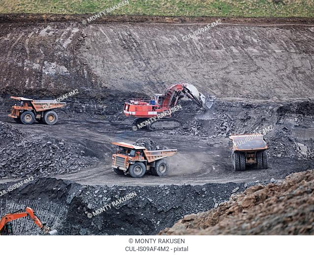 Diggers and dumper trucks at work in surface coal mine