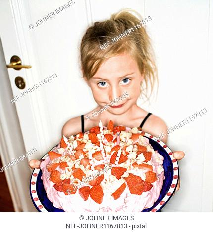 Portrait of girl holding strawberry birthday cake