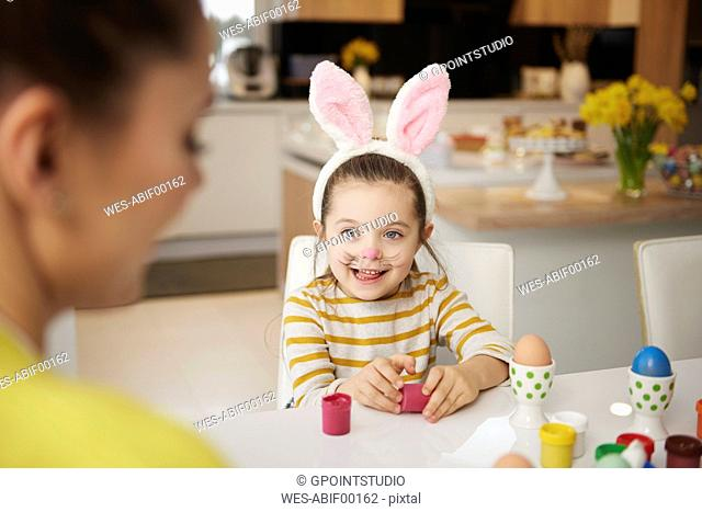 Girl with bunny ears and mother sitting at table with Easter eggs