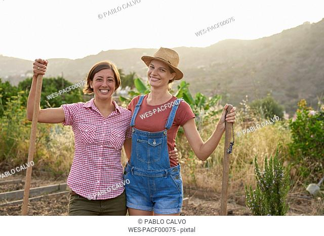 Portrait of two happy farmers with shovels