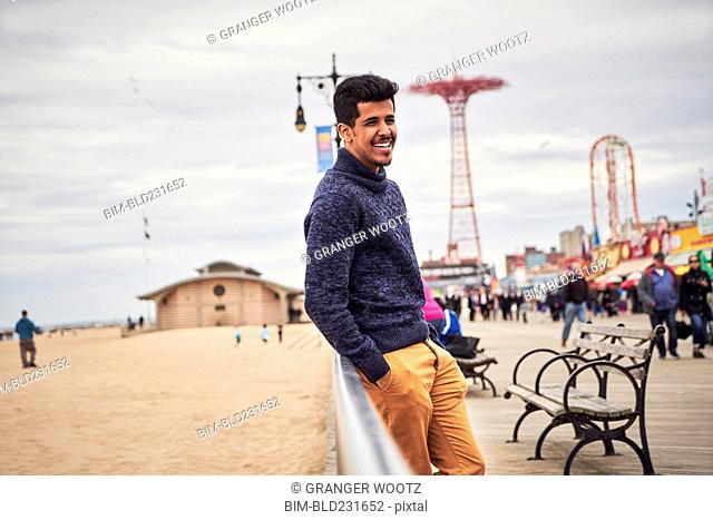 Man leaning on boardwalk railing at beach