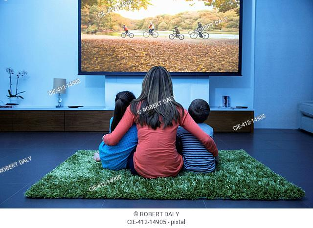 Mother and children watching television in living room