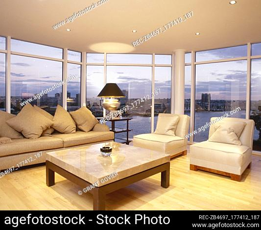 Sitting room with wood floor, coffee table, and a sofa and chairs in front of picture windows with a city view