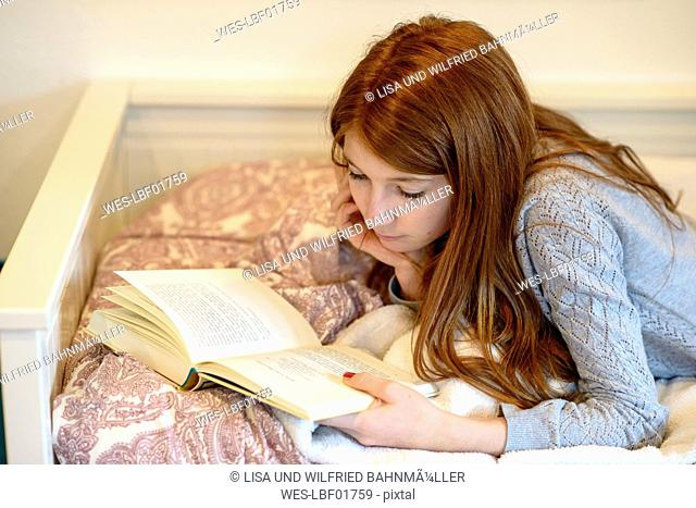 Redheaded teenage girl lying on bed reading a book