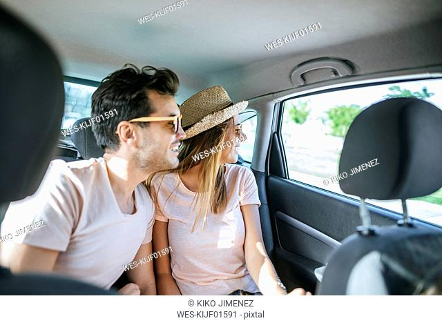 Couple in the back seat of a car looking out the window
