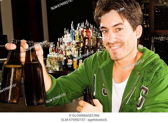 Portrait of a young man holding beer bottles at a bar counter and smiling