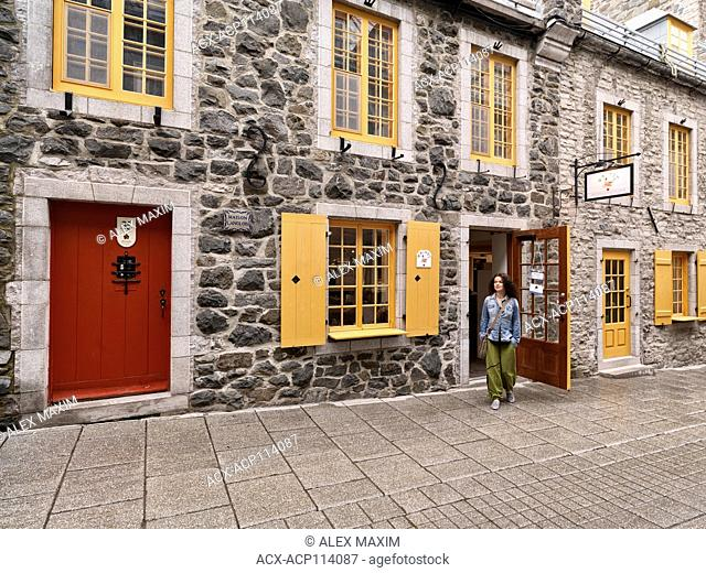 Young woman in front of the Amimoc Native American shoe store on Rue Petit Champlain historic street in Old Quebec City at daytime, Canada