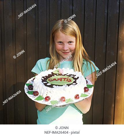 Pre teen girl holding birthday cake
