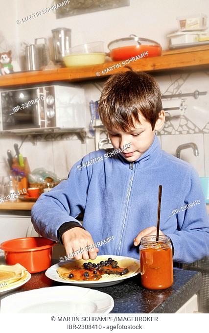 Boy making Palatschinken, pancakes