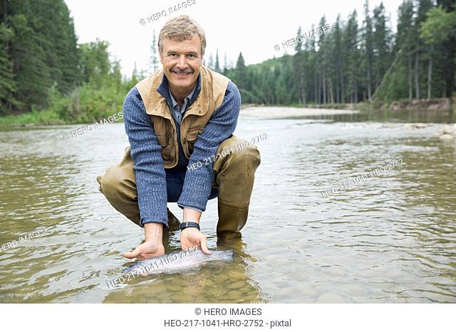 Portrait of mature man holding caught fish
