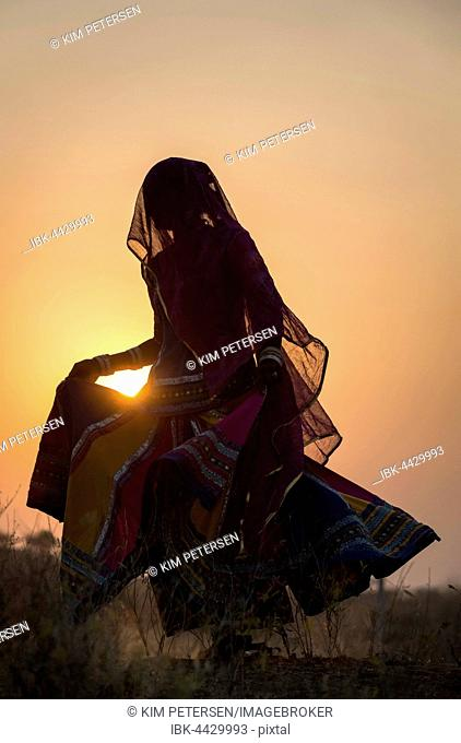 Woman dancing in front of the sun, Pushkar, Rajasthan, India