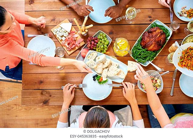 thanksgiving day, eating and leisure concept - group of people having dinner at table with food