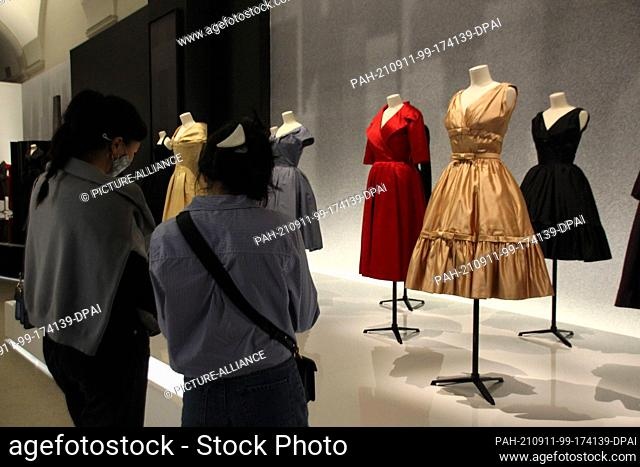 10 September 2021, US, New York: Visitors look at dresses from the exhibition honoring French fashion designer Dior at the Brooklyn Museum