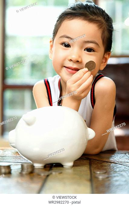 Girl dropping coin into saving box