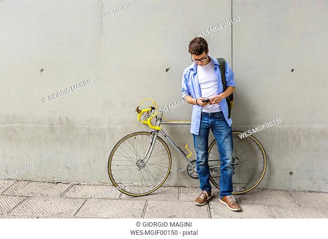 Young man with racing cycle looking at cell phone in front of concrete wall