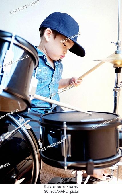 Male toddler playing drum kit