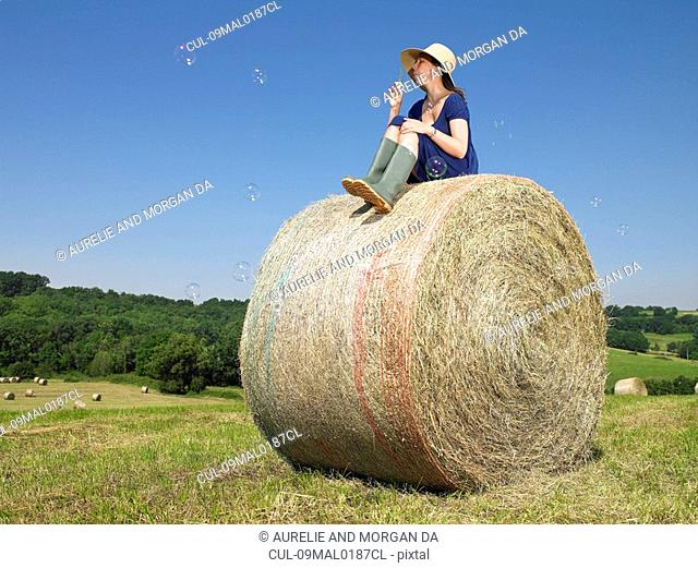 Girl on bale of hay blowing bubbles